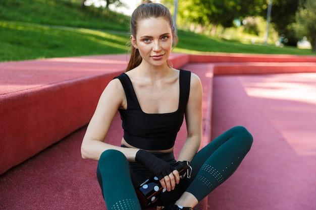 緑豊かな公園でのトレーニング中にスポーツグラウンドに座っている間魔法瓶を保持しているトラックスーツを着ているスリムな若い女性の肖像画