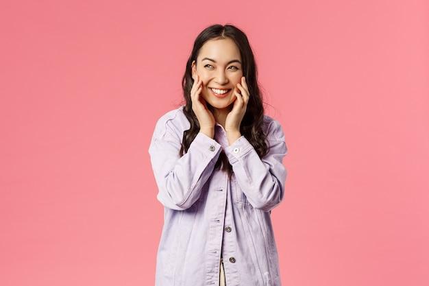 Портрет хитрой и креативной симпатичной азиатской подруги о чем-то думает, хихикает, раздумывая коварный план, отводит взгляд трогательно щеками и коварно хихикает, стоя на розовом фоне