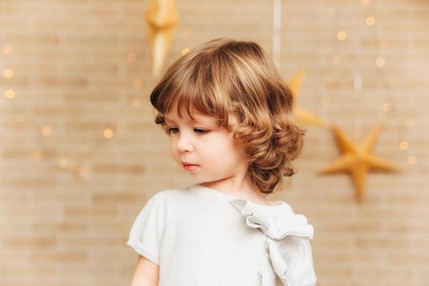Портрет маленькой девочки с каштановыми вьющимися волосами и большими голубыми глазами
