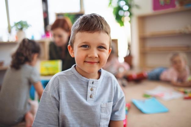 카메라를 찾고 교실에서 실내 작은 보육 학교 소년의 초상화.