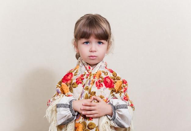Портрет маленькой красивой девушки в традиционных украинских костюмах на белом фоне