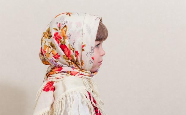 전통적인 우크라이나 스타일에 작은 예쁜 여자의 초상화. 길고 흰 국가 셔츠와 전통적인 스카프에 젊은 아름 다운 소녀. 우크라이나 문화, 민족 스타일