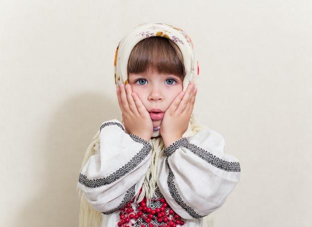 Портрет маленькой довольно удивленной девушки в традиционном украинском костюме на белом фоне