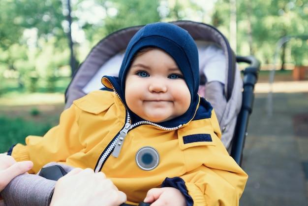 公園のベビーカーに座っている小さな幼児、黄色のジャンプスーツの赤ちゃんの肖像画