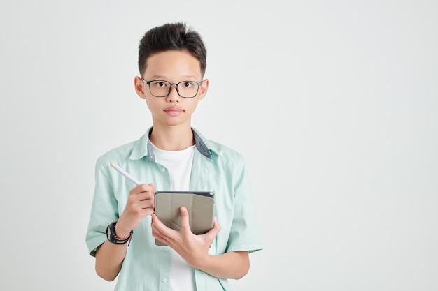 Портрет умного азиатского ребенка, рисующего на планшетном компьютере со стилусом, изолированный на светло-сером