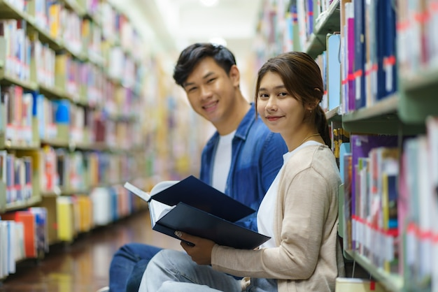 一緒に本を読んでスマートアジアの男女の大学生の肖像画と。コピースペースのあるキャンパスライブラリの本棚の間のカメラを見ています。