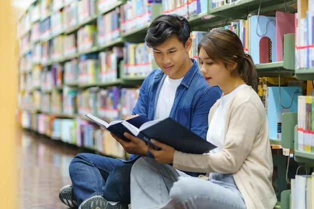 コピースペースのあるキャンパス図書館の本棚の間で一緒に本を読んでいるスマートアジアの男性と女性の大学生の肖像画。