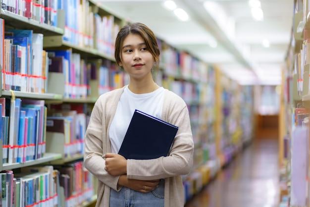 本を読んで、コピースペースのあるキャンパスライブラリの本棚の間でカメラを見ているスマートアジアの女性大学生の肖像画。