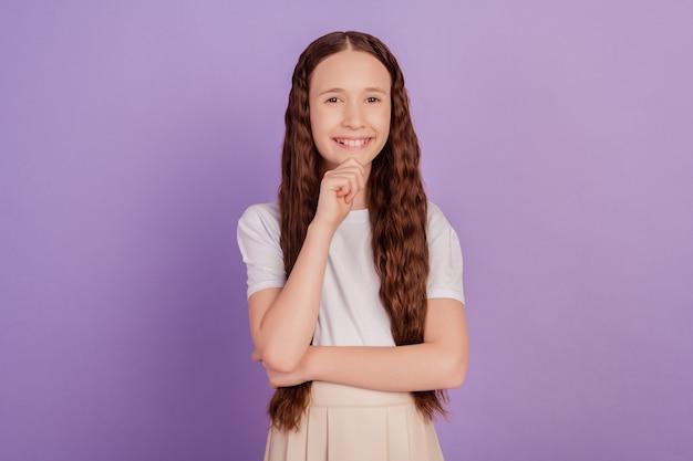 보라색 배경에 빛나는 미소를 비추는 똑똑한 영리한 여학생 손가락 턱의 초상화