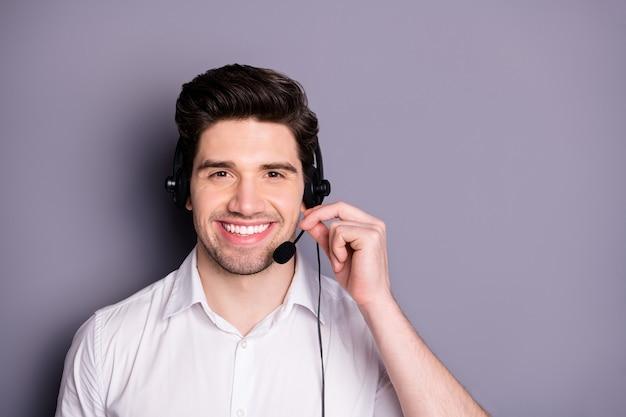 스마트 자신감 콜센터 작업자 남자 착용 이어폰의 초상화는 고객이 회색 벽 위에 절연 정장 의류를 착용하는 데 도움이 될 수 있습니다.
