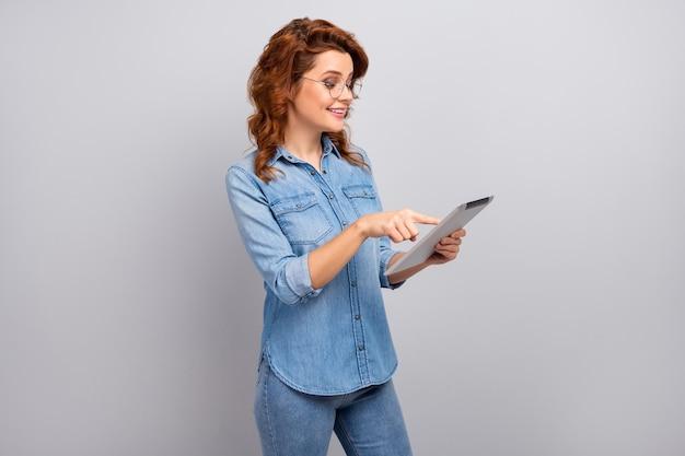 スマートな自信を持っている女性の肖像画はタブレットを使用しますソーシャルメディアのニュースを読みます指のタッチスクリーンをフォローします灰色の壁の上に隔離された見栄えの良い服を着ます