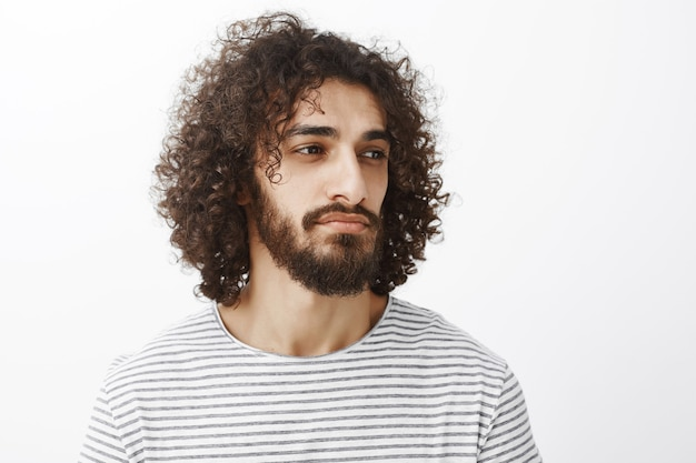 Портрет умного тупого привлекательного бородатого мужчины с вьющимися волосами, который смотрит прямо, думая или расставаясь с легкой улыбкой