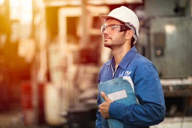 Портрет умного работника книги руководства по обслуживанию машины образования инженера счастливого стоящего гордо стоящего в предпосылке тяжелой промышленности.