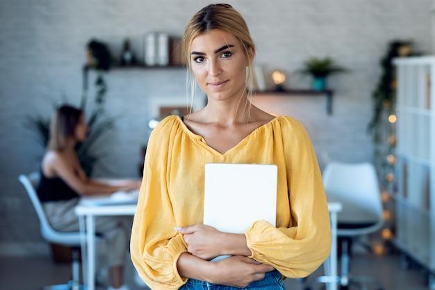 彼女のスタートアップ中小企業でカメラを見ながらデジタルタブレットで作業しているスマートなフリーランスのビジネス女性の売り手の肖像画。