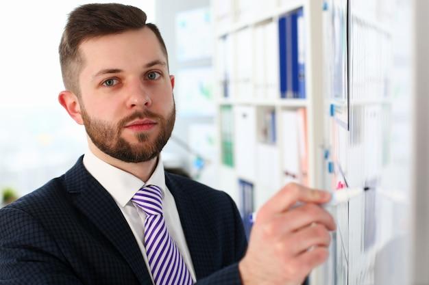 고급스러운 양복을 입고 찾고 스마트 남성의 초상화. 매력적인 기업 관리자 단단히 쓰기 펜을 들고 현대 사무실에서 포즈. 회사 회의 개념