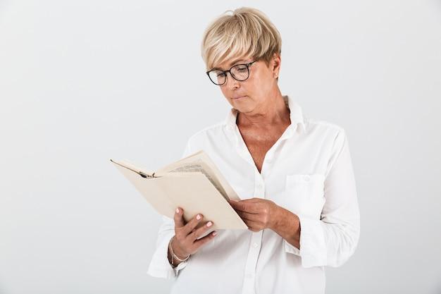 Портрет умной женщины средних лет в очках, читающей книгу, изолированную над белой стеной в студии