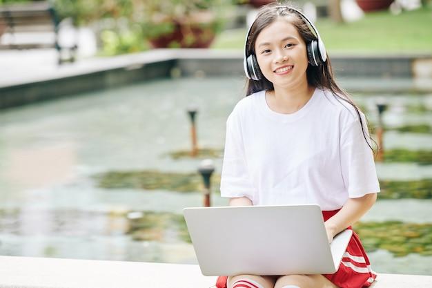 キャンパスでラップトップで作業するときにヘッドフォンを身に着けているスマートな10代の少女の肖像画