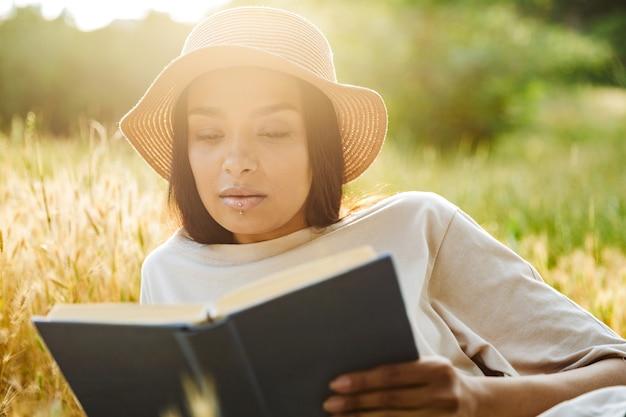 Портрет умной женщины с пирсингом в губе и соломенной шляпе, читающей книгу, лежа на траве в зеленом парке