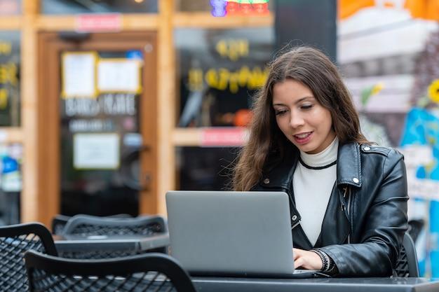 Портрет умной молодой женщины с ноутбуком, работающей над ноутбуком в кафе на открытом воздухе, концепция работы из любого места