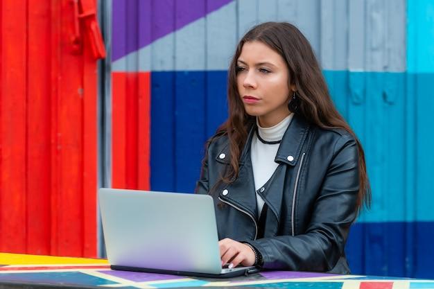 Портрет умной молодой женщины с ноутбуком, работающей на ноутбуке в кафе на открытом воздухе, концепция работы из любого места