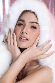 패션에 있는 미소 아시아 여성의 초상화는 얼굴 눈 사랑 하트 스타일 봄 여름, 흰색 모피 검은 머리, 스튜디오 조명 분홍색 은색 패브릭 배경 복사 공간, 소셜에 합류하기 위한 컨셉 럭셔리