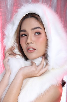 패션에 있는 미소 아시아 여성의 초상화는 스타일 흰색 모피 검은 머리, 스튜디오 조명 분홍색 은색 패브릭 배경 복사 공간, 사교 밤 행사에 참여할 수 있는 컨셉 럭셔리