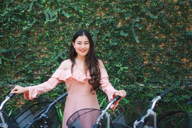 벽에 신선한 녹색 담쟁이 잎이 달린 자전거를 들고 서서 웃고 있는 행복한 아시아 여성의 초상화. 활동을 이완하십시오.
