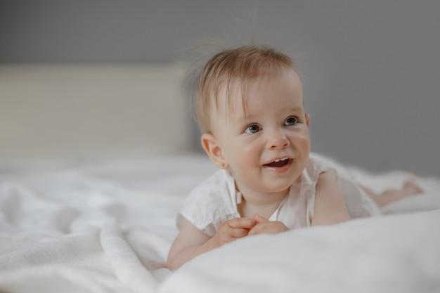 Портрет улыбнувшейся удивленной маленькой милой девочки с большими глазами, лежащей на белой простыне.