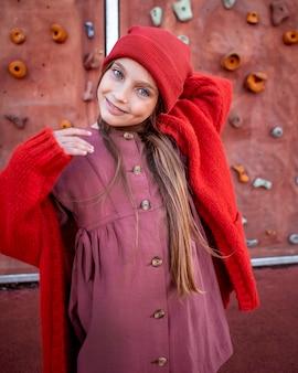 Портрет улыбающейся девушки, стоящей рядом со скалодромом