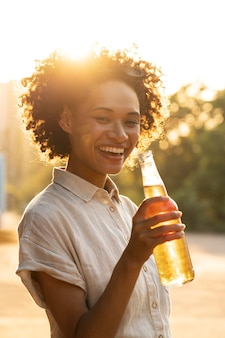 ビールを持っている日光の下で屋外で笑顔の幸せな女の肖像画