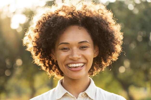 Портрет счастливой женщины смайлик на открытом воздухе в солнечном свете