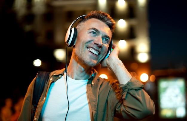 헤드폰으로 밤에 도시에서 웃는 남자의 초상화
