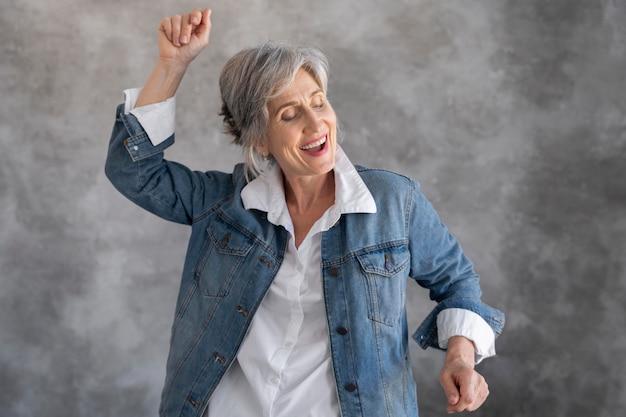 ジーンズジャケットのスマイリー年配の女性の肖像画