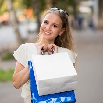 買い物袋を保持しているスマイリー女性の肖像画