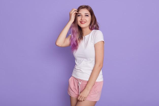 흰색 티셔츠와 핑크색 반바지를 입고 카메라를보고 그녀의 머리를 만지고, 라일락 배경 위에 고립 된 행복을 표현하는 웃는 사랑스러운 소녀의 초상화.