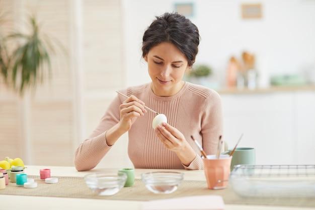 居心地の良いキッチンインテリア、コピースペースのテーブルに座ってイースターエッグを描く笑顔の大人の女性の肖像画