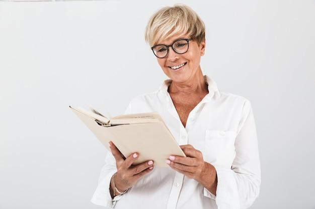 Портрет улыбающейся взрослой женщины в очках, читающей книгу, изолированную над белой стеной в студии