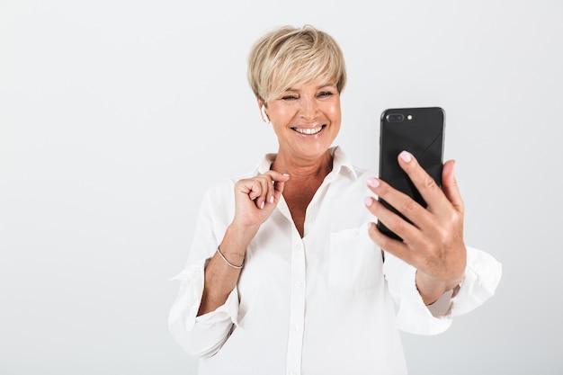 スタジオで白い壁の上に分離されたイヤポッドと携帯電話を使用して短いブロンドの髪の笑顔の大人の女性の肖像画