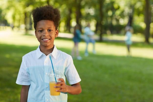 屋外の緑豊かな公園に立っている間オレンジジュースを保持している笑顔のアフリカ系アメリカ人の少年の肖像画