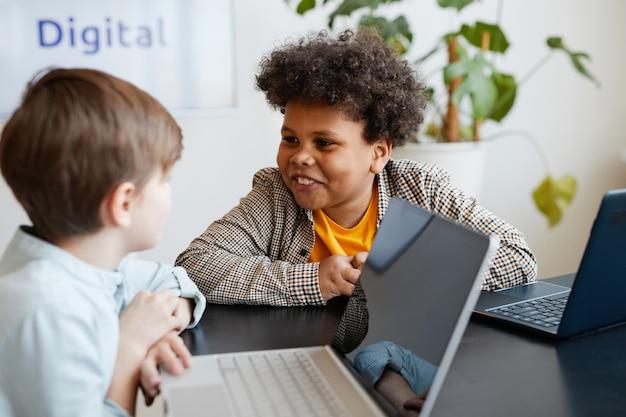 学校の授業中に友人と話している笑顔のアフリカ系アメリカ人の少年の肖像画