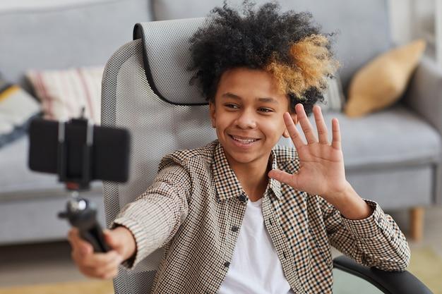自宅から自撮り棒とビデオブログを保持しながらカメラに手を振っている笑顔のアフリカ系アメリカ人の少年の肖像画、コピースペース