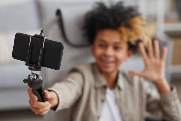 自宅からスマートフォンとビデオブログで自撮り棒を保持しながらカメラに手を振っている笑顔のアフリカ系アメリカ人の少年の肖像画、前景に焦点を当て、スペースをコピー