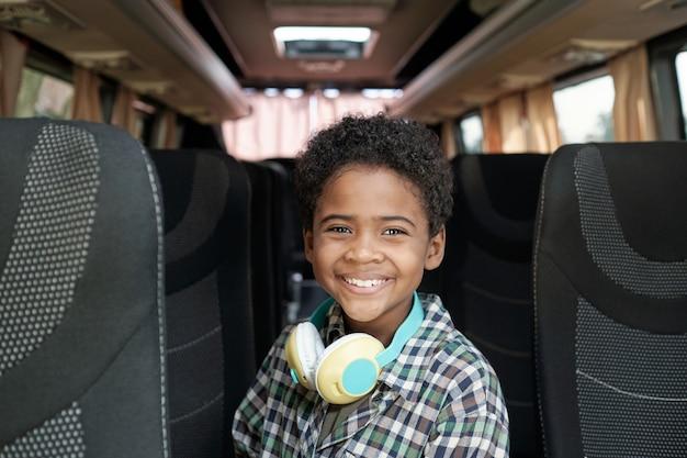 Портрет улыбающегося афро-американского мальчика с наушниками на шее, стоящего в проходе автобуса