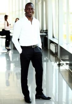 バックグラウンドで働く幹部と笑顔のアフリカ系アメリカ人ビジネスマンの肖像画