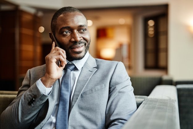 出張中にホテルのロビーでスマートフォンで話すアフリカ系アメリカ人のビジネスマンの笑顔の肖像画、コピースペース
