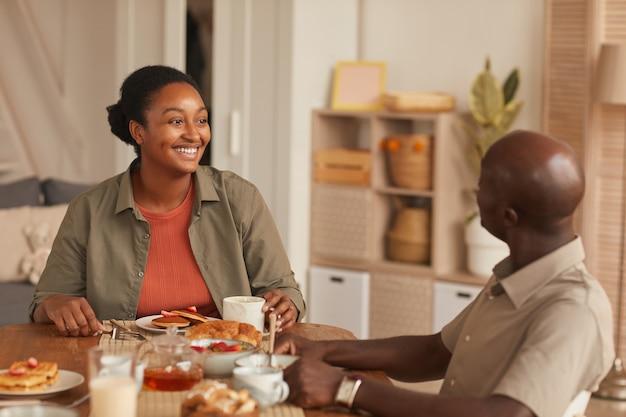 自宅で家族と一緒に朝食を楽しみながらダイニングテーブルに座って笑顔のアフリカ系アメリカ人カップルの肖像画