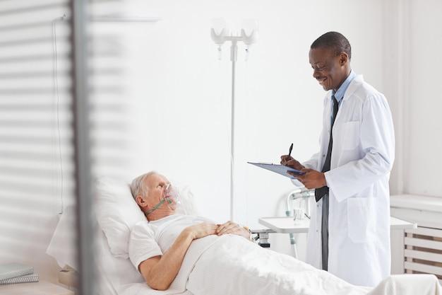 Портрет улыбающегося афро-американского врача, ухаживающего за пожилым мужчиной, лежащим на больничной койке с кислородной маской, копией пространства