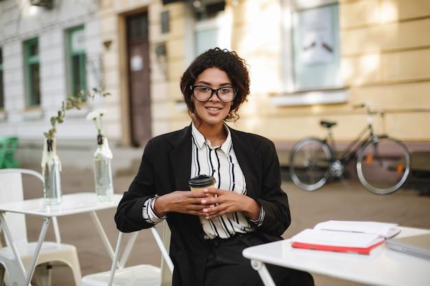 カフェのテーブルに座って幸せにメガネで笑顔のアフリカ系アメリカ人の女の子の肖像画