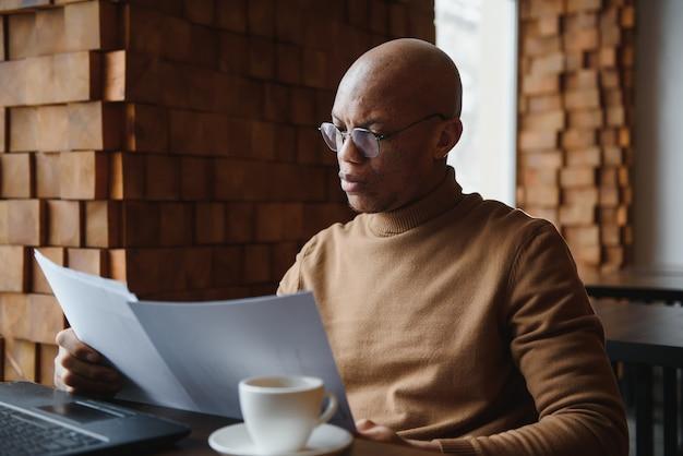 Портрет улыбающегося афро-американского мужчины в очках, сидящего за столом в офисе, работающего на ноутбуке, счастливый двухрасовый мужчина-работник смотрит на камеру, позирует, занятый использованием современного компьютерного гаджета на рабочем месте