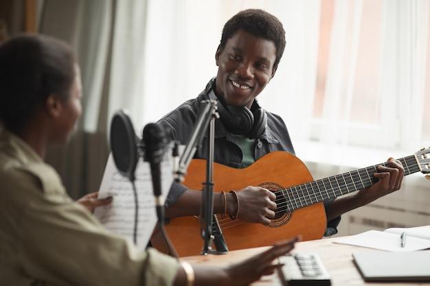 Портрет улыбающегося афроамериканца, играющего на гитаре во время записи музыки дома, копией пространства